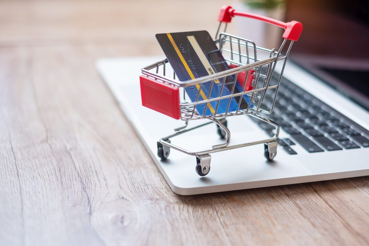 e-commerce solution shopping cart holding a credit card on a laptop